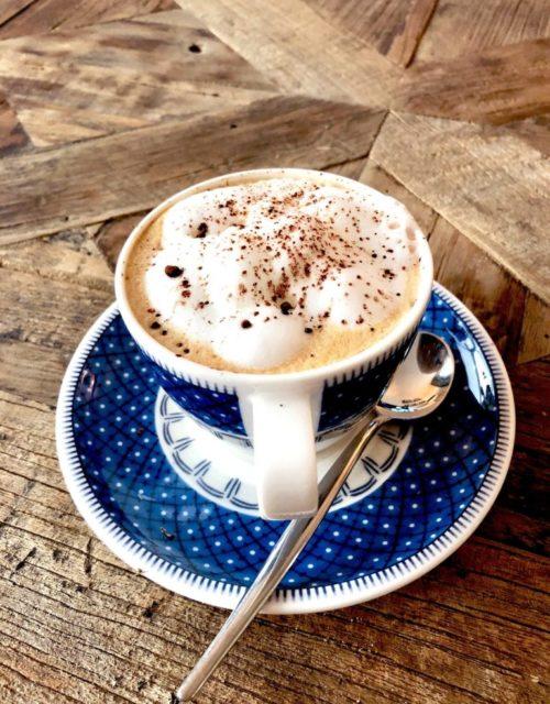 Kaffee in einer blauen Tasse auf einem Holztisch.