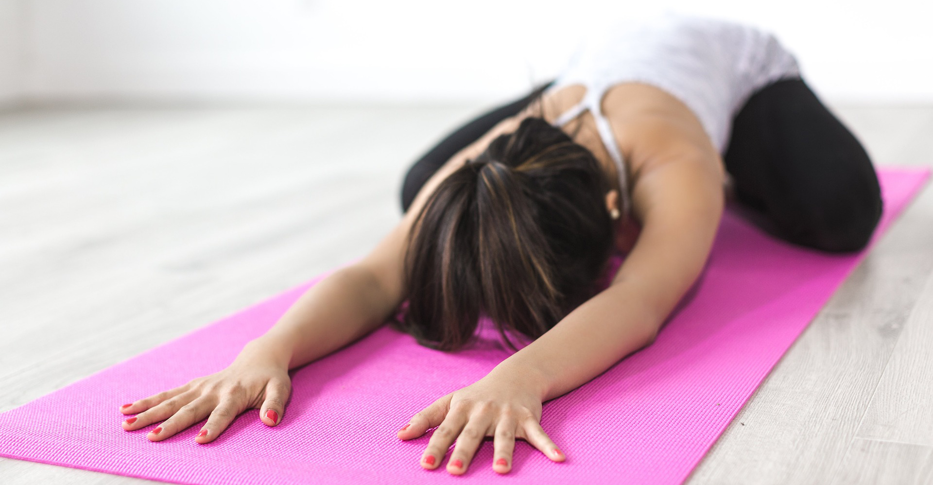 Frau in Kindshaltung auf Yogamatte.
